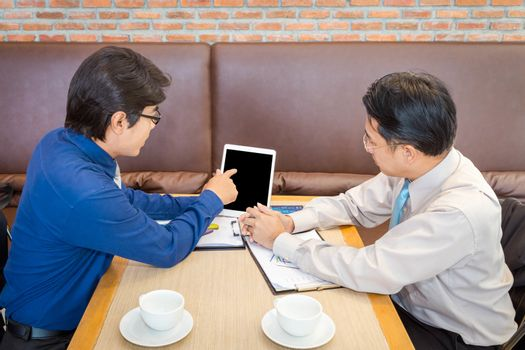 Two Asian businessmen discussing using tablet