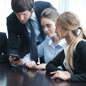 Group of business people working at office and using smartphone