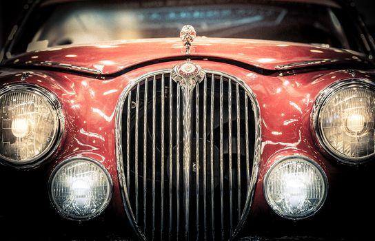Front headlights and grille of a vintage Jaguar.