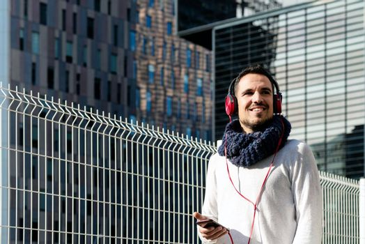 Young bearded man with headphones and holding smartphone while walking against skyscrapers in sunny day