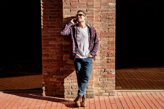 Young bearded male leaning on a bricked wall wearing sunglasses while using a smartphone outside.