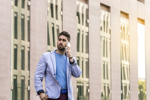 Portrait of cheerful modern businessman speaking by phone and smiling while standing outdoors