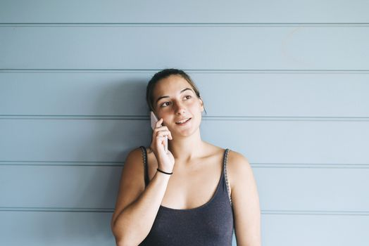 Young adult female in summer dress talking on cell phone while leaning against wood paneled wall