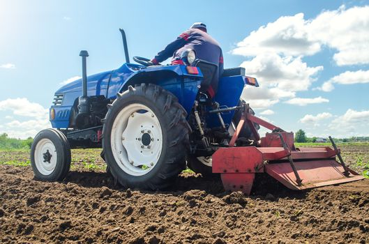 Farmer on a tractor with a milling machine processes loosens soil in the farm field. Preparation for new crop planting. Grind and mix soil on plantation. Loosening surface, cultivating the land.