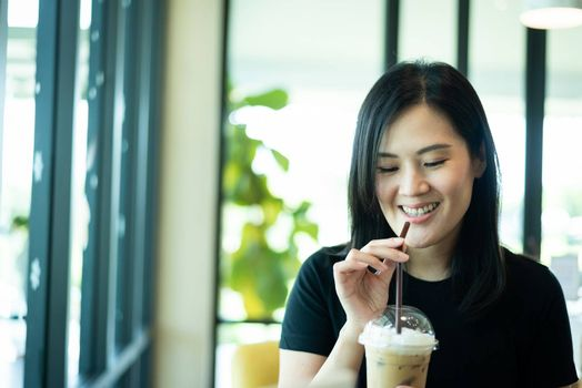 An Asian beautiful woman has drinking an ice cappuccino in the morning.