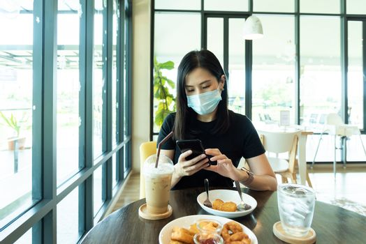 An Asian beautiful woman has to wear a blue mask and prepare to start breakfast in the coffee cafe with new normal and social-distancing.