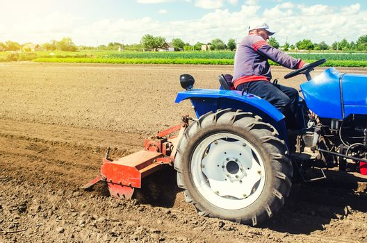 A farmer on a tractor works the field with a shredder in preparation for planting a new crop. Loosens, grind and mix soil. Moldboard loosening surface. Farming, agriculture. Plowing.