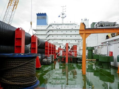 The deck lay barge. Pipes and Lifting cranes on the ship. Equipment for laying a pipeline on the seabed.
