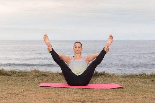 Woman in sportswear doing pilates outdoor on a pink mat with the sea in the background.