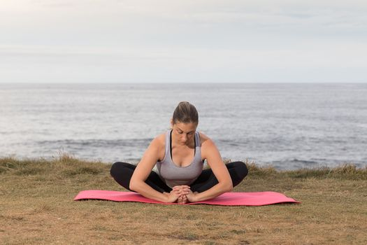 Woman in sportswear exercising outdoor on a pink mat with the sea in the background.