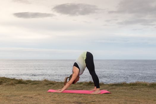 Woman in sportswear doing yoga outdoor on a pink mat with the sea in the background.