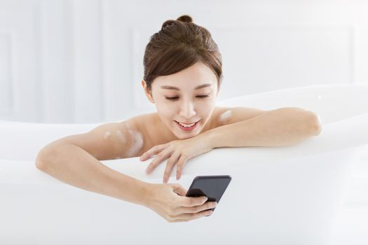young woman take a bath and watching the mobile phone in bathtub