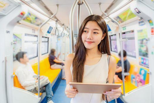 Young Asian woman passenger using mutimedia player via Technolog