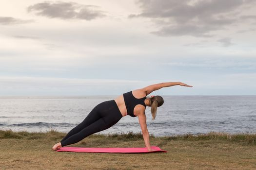 Woman in black sportswear doing pilates outdoor on a pink mat with the sea in the background.