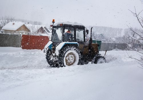 During heavy snowfall, the tractor clears the snow-covered road.
