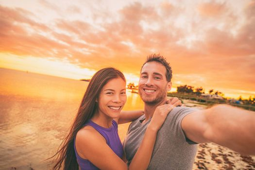 Happy selfie couple tourists on USA travel taking photo at sunset on Florida beach. Smiling Asian woman and Caucasian man, interracial relationship.
