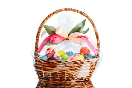 Easter gift basket with multicolor eggs, isolated on white