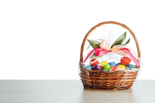 Easter gift basket with multicolor eggs, white background