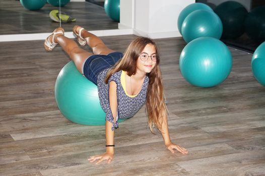 teenager girl with fitness ball in gym.