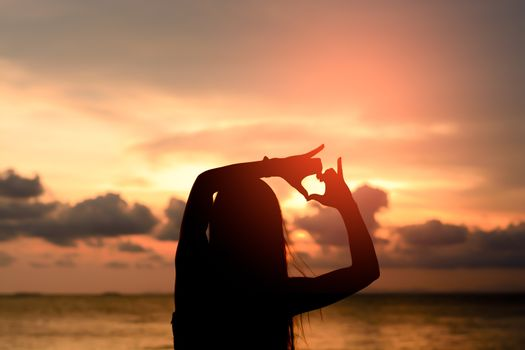 woman hands forming a heart with sunset silhouette