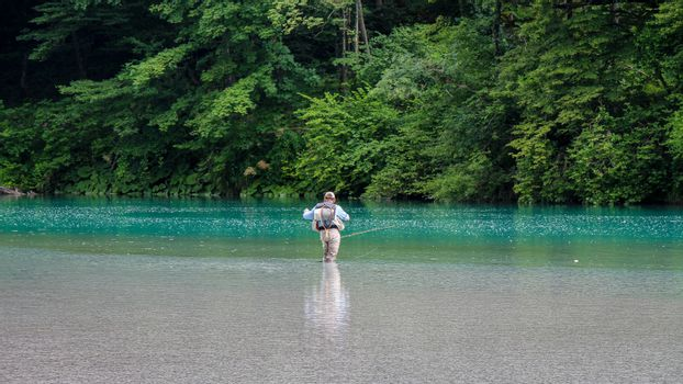 Tolmin, Slovenia - July 18th 2018: A man wading in the Soca River, while fly fishing, at the Tolminka River confluence, Tolmin, Slovenia