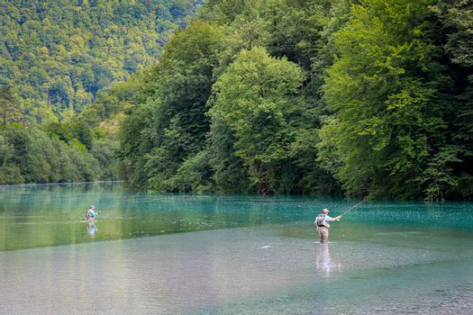 Tolmin, Slovenia - July 18th 2018: Two fly fisherman fishing for Marble Trout on the Soca River at the Tolminka River Confluence, at Tolmin, Slovenia