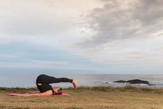 Woman in sportswear doing pilates outdoors on a pink mat with the sea in the background.