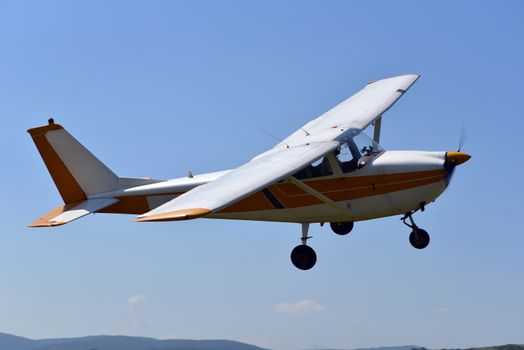 A small sports single-engine plane is flying