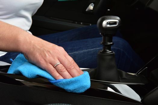 Cleaning the car console with a microfiber cloth
