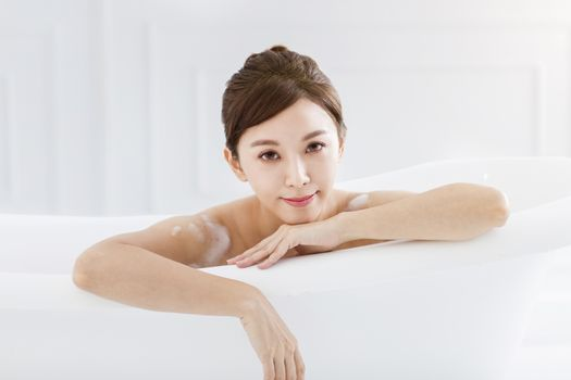 Beautiful young asian woman relaxing in bathtub