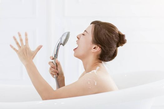 young woman take a bath and singing in the bathtub
