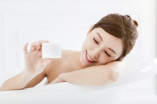 Woman in bathtub and  showing blank bathing product