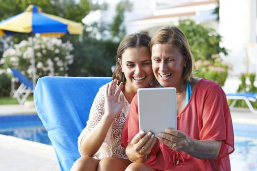Mother and Daughter keeping in touch with friends and family using a digital tablet while on holiday