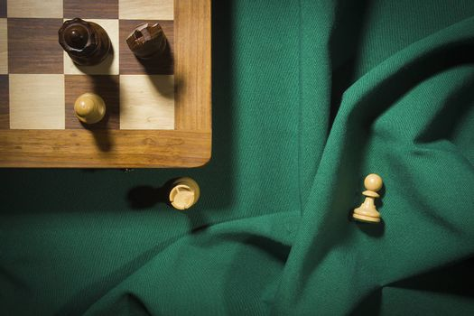 Wooden chess and chess board on green cloth