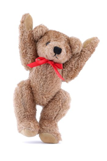 A jumping brown Teddy bear with red ribbon on white background