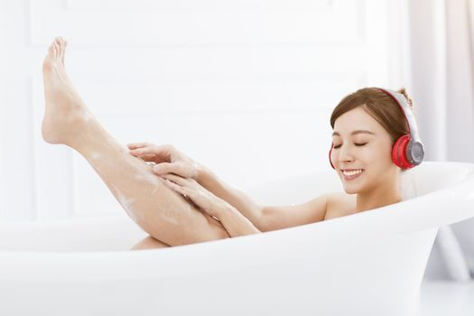 young woman with headphones relaxing in bathtub