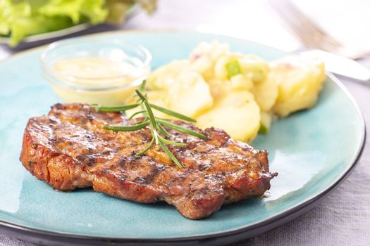 grilled pork steak with potato salad