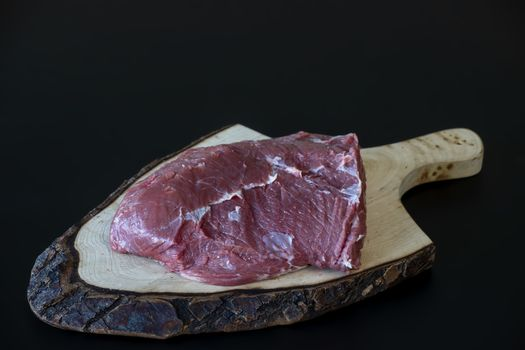 raw meat on wooden chopping board