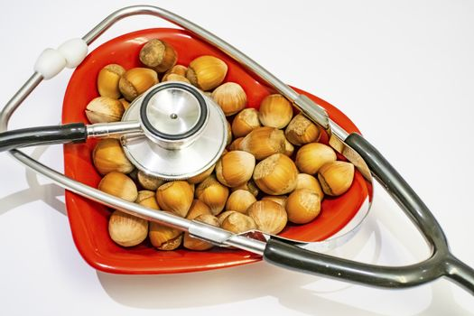 shelled hazelnut heart figured on red plate and stethoscope for human health