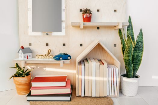 Home decor cozy wall shelves with books and toy car. New house decoration concept. Plants, wooden shelf, happy sign.