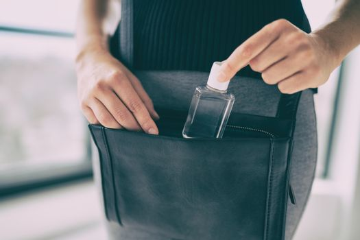 Small hand sanitizer bottle to go in woman's purse. Girl using portable sanitiser in bag, when going on commute, for disinfecting hands as COVID prevention.