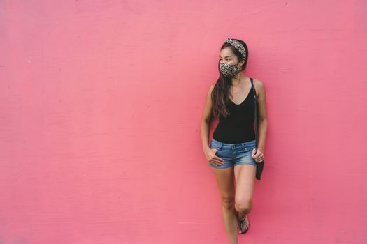 Asian woman leaning on pink wall wearing fabric face mask in fashion leopard pattern print. Casual young people city lifestyle during corona virus.