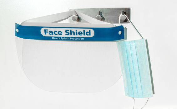 PPE supplies face shield direct splash protection and mask hanging on hooks. New clean corona virus protective equipment ready to use for coronavirus prevention.