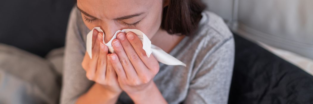 Sick woman feeling unwell at home. Young girl with flu symptoms coughing in tissue covering nose when sneezing as COVID 19 prevention. Panoramic crop.