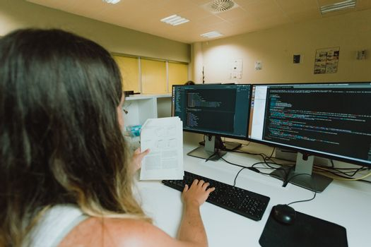 Young female worker in front a dual screen computer testing information