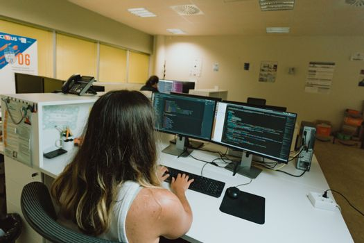 Young female worker in front a dual screen computer in the office
