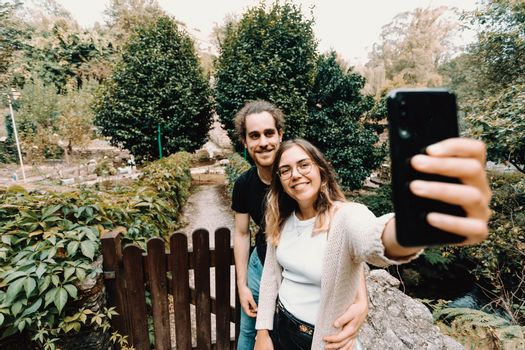 Young and smiling couple taking a selfie in front of a beautiful rural house