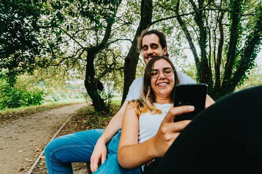 A close up of a young couple looking the mobile phone while sitting on a bench in the park