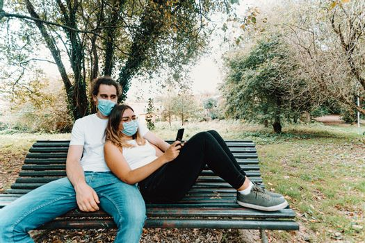 A young couple with the masks on resting in a bench while looking the phone in the park