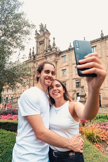 A vertical shot of a young couple taking a fancy selfie in a garden in front of an old building